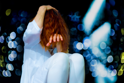 kvinna som sitter ihopkrupen med nedsänkt huvud